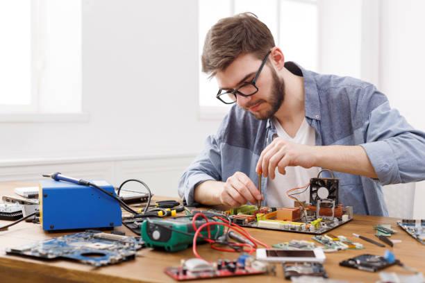 Фото мастер по ремонту компьютеров работает над материнской платой