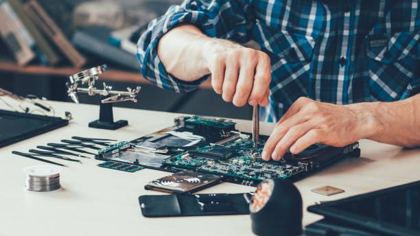 Фото мастер по ремонту компьютеров работает над диагностикой материнки ноута