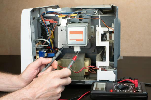 Фото Мастер проверяет почему микроволновка перестала включаться