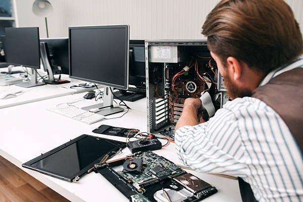 Фото мастер по ремонту компьютеров работает над подключением жесткого диска
